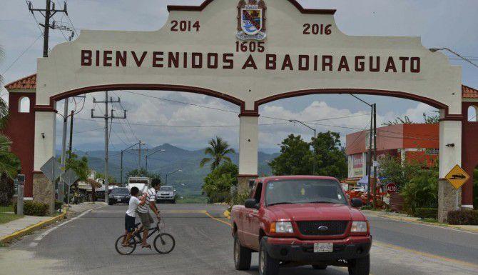 """Una camioneta pasa por la entrada a Badiraguato, Sinaloa, la cuna de Joaquín """"El Chapo' Guzmán. El poblado donde se topan las pladeras de la costa y la Sierra Madre, está sumido en la pobreza. (AP/FERNANDO BRITO)"""