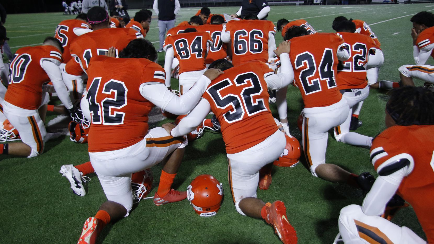 Following a talk by head coach Bobby Estes, North Dallas players pause for a prayer following their 12-7 loss to Roosevelt on October 29, 2020. (Steve Hamm/ Special Contributor)
