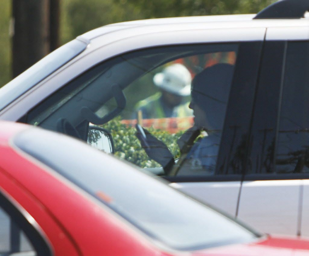 A woman uses her mobile phone while stopped at Collins Road and Interstate 30 in Arlington. The city enacted a law against texting while driving in 2011 and provides for a fine of as much as $200. Fines included in a new state law that will take effect Sept. 1 are generally lower but can be as high as $200 for repeat offenders.