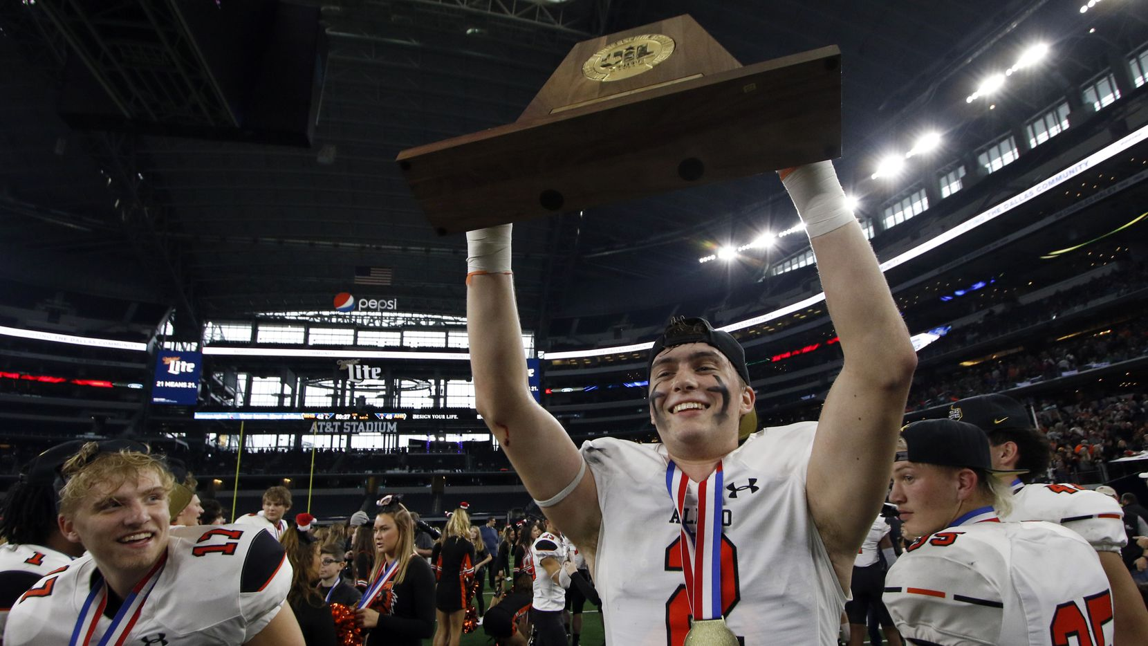 Flanked by Bearcats teammates Kevin Andridge (17) and Sam Forman (35), receiver Jaedon Pellegrino (2) lifts the state trophy following the Bearcat's 45-42 victory over Fort Bend Marshall. The two teams played their Class 5A Division ll state championship football game at AT&T Stadium  in Arlington on December 21, 2019. (Steve Hamm/ Special Contributor)