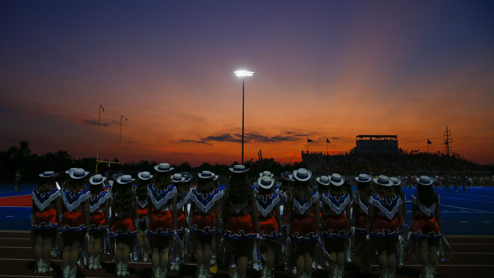 The sun sets beyond the Parish Episcopal drill team during a high school football game between Parish Episcopal of Dallas and Trinity Christian of Cedar Hill. The game was at Parish Episcopal.