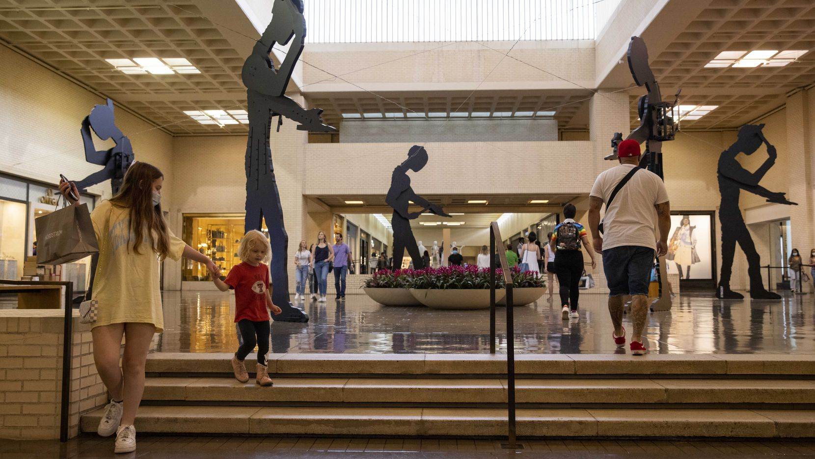 Shoppers walk by the Five Hammering Men by Jonathan Borofsky at NorthPark Center on a recent afternoon in May.