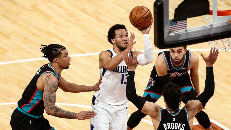 Dallas Mavericks guard Jalen Brunson (13) shoots from between Memphis Grizzlies forward Dillon Brooks (24) and Brandon Clarke, left, during the second half of an NBA basketball game Tuesday, May 11, 2021, in Memphis, Tenn.