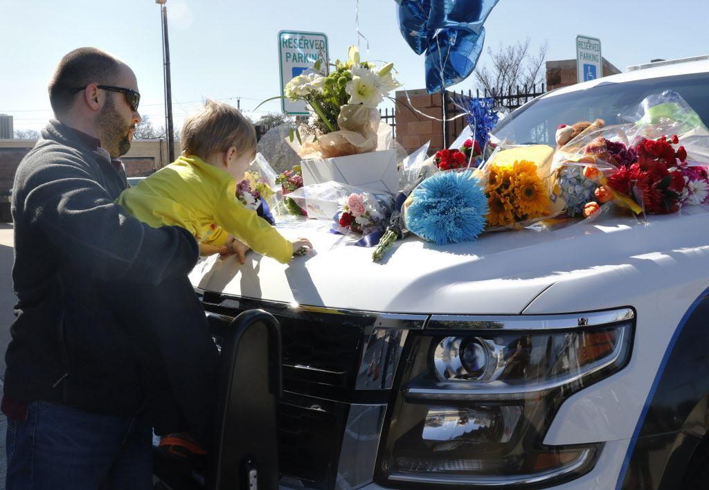 Kevin Goldsmith y su hijo Henry dejan flores en un patrullero policial en homenaje a David Sherrard, el policía de Richardson, fallecido el miércoles. (DMN/DAVID WOO)
