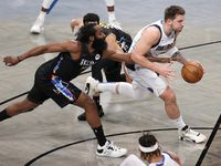 Luka Doncic #77 of the Dallas Mavericks dribbles as James Harden #13 of the Brooklyn Nets defends during the first half at Barclays Center on February 27, 2021 in the Brooklyn borough of New York City.