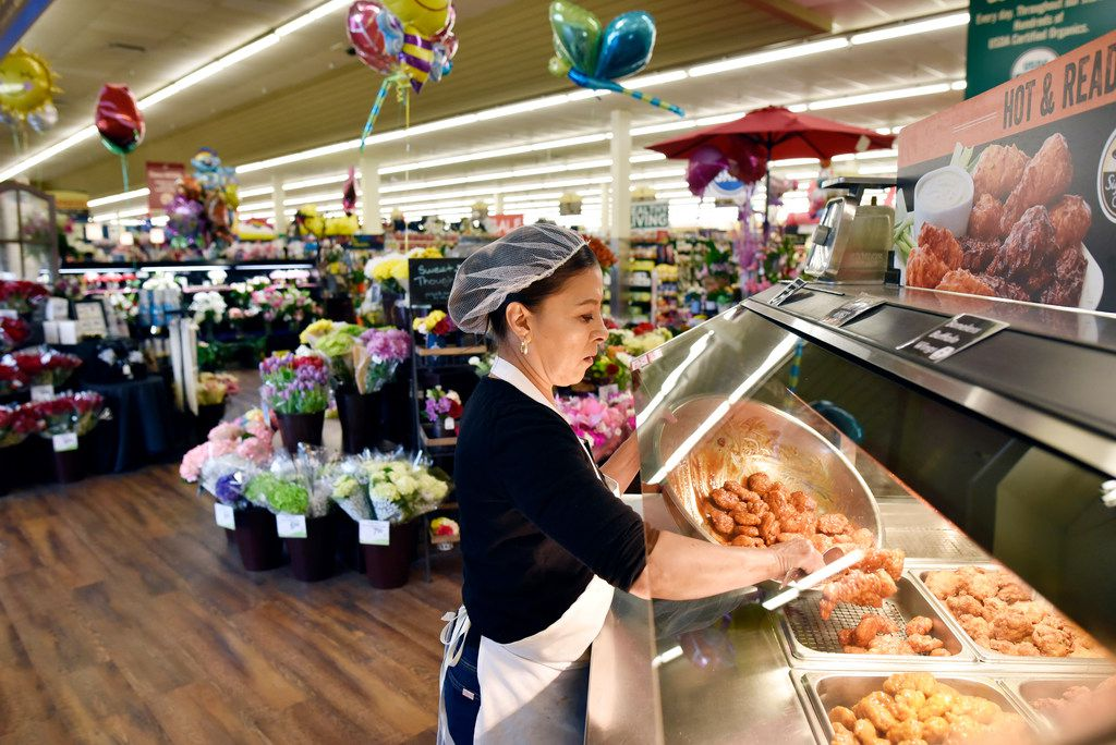 Anna De Leon, an Albertsons deli clerk, stocks fresh hot wings at the hot wing bar inside the Albertsons at the Casa Linda shopping center in Dallas.