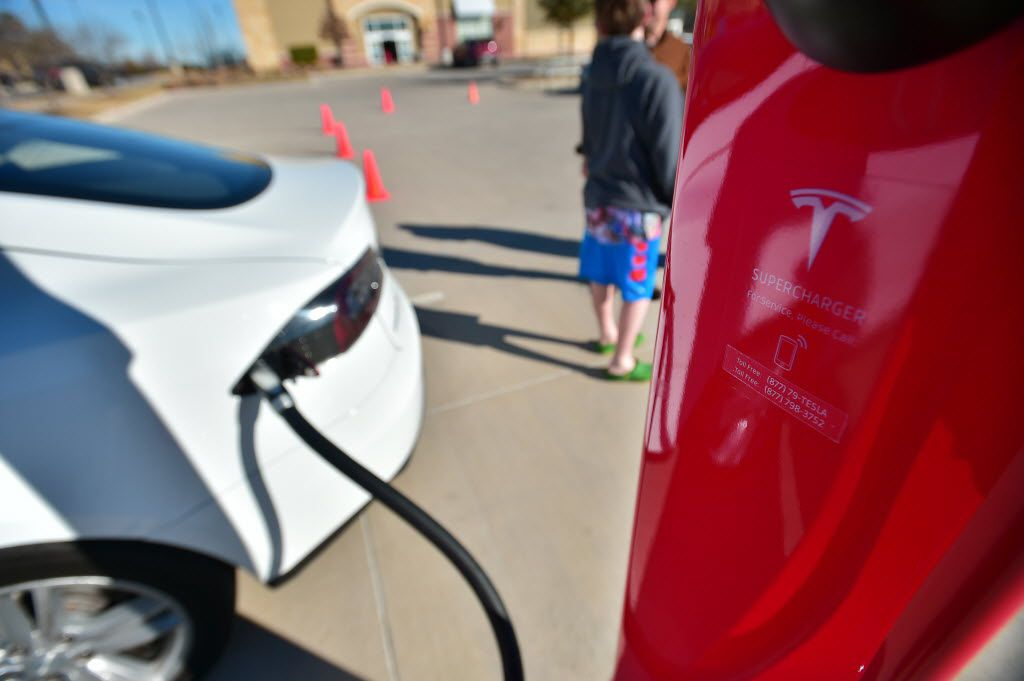 More than two dozen North Texas Tesla owners gather at the grand opening of the new Tesla Supercharger electric car charging station at the Rayzor Ranch shopping center on University Drive on  Jan. 30, 2016, in Denton.