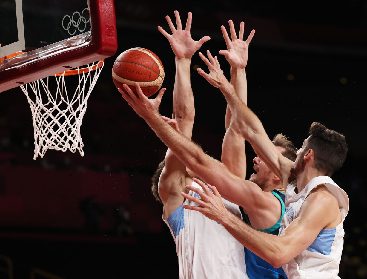 Slovenia's Zoran Dragic (30) attempts to score as he is defended by Argentina's Leandro Nicolas Bolmaro (10) and Francisco Caffaro (11) during the postponed 2020 Tokyo Olympics at Saitama Super Arena on Monday, July 26, 2021, in Saitama, Japan. Slovenia defeated Argentina 118-100. (Vernon Bryant/The Dallas Morning News)
