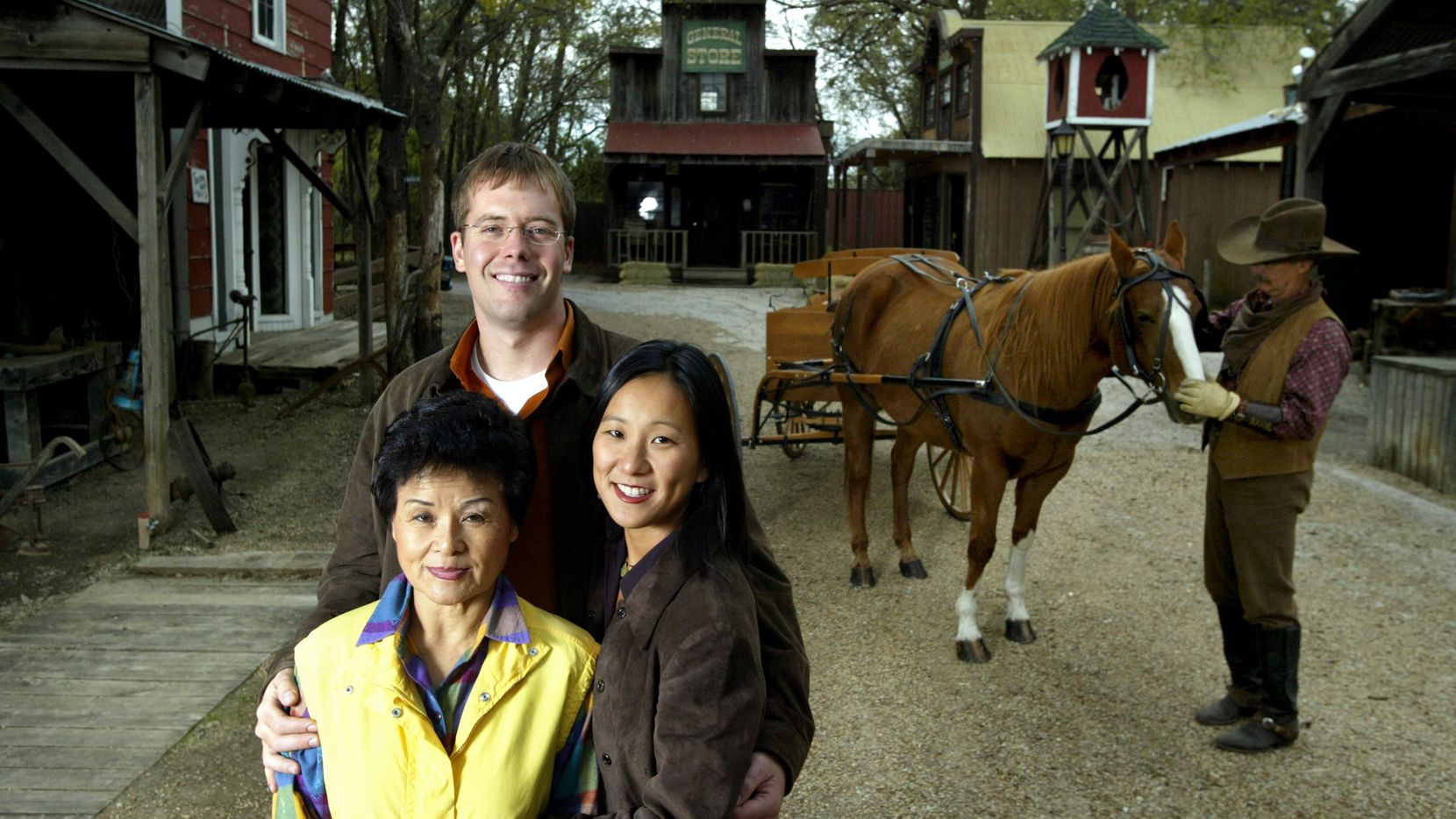 President of Storybook Ranch Jeong Nim Kim (lower left), with her daughter Lynn Miller and son-in-law Brandon Miller, who were general managers for the authentic multi-million dollar Western town assembled in 1981 in McKinney.  Their 'Ranch Cowboy' Gary Drake, far right, nuzzles with his horse Mississippi.