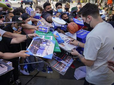 Dallas Mavericks guard Luka Doncic signs autographs for fans as he leaves the team hotel before an NBA playoff basketball game against the LA Clippers on Wednesday, June 2, 2021, in Los Angeles.
