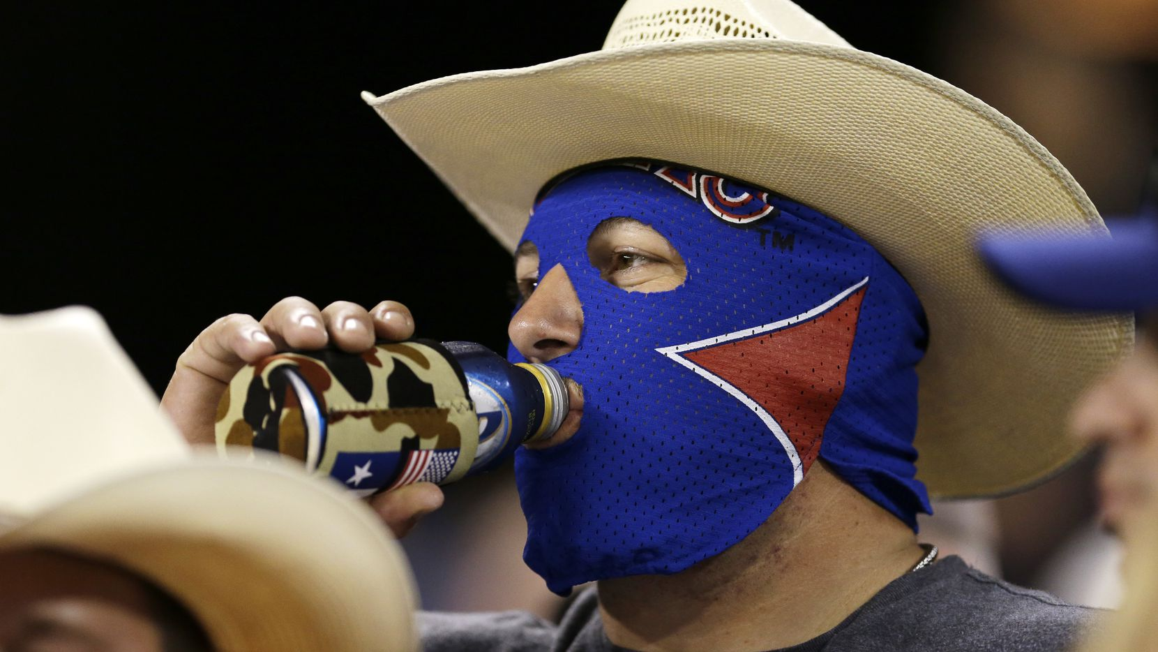 A Texas Rangers fan wearing a cowboy hat and a wrestling mask drinks beer during a baseball game against the Seattle Mariners, Monday, Aug. 26, 2013, in Seattle. (AP Photo/Ted S. Warren)