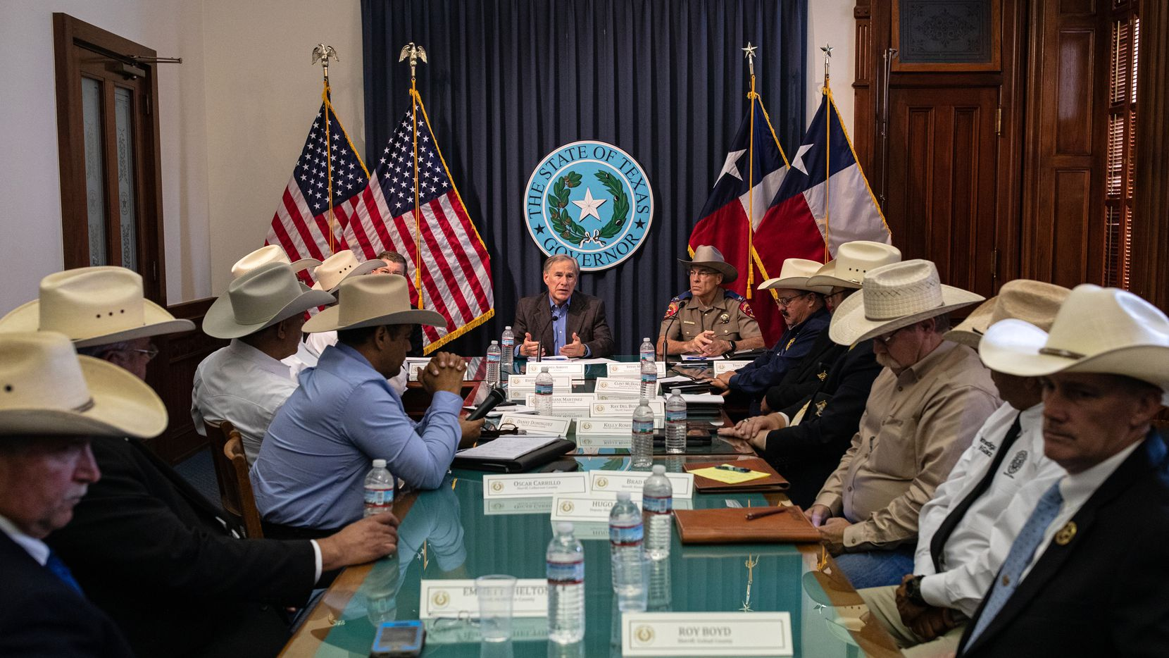 Gov. Greg Abbott, shown with border community sheriffs at the Texas Capitol on July 10, was tested for COVID-19 on Thursday, and got a negative result. Abbott took the test a day after a Florida politician who attended his weekend border security event in Del Rio announced she'd become infected by the virus.