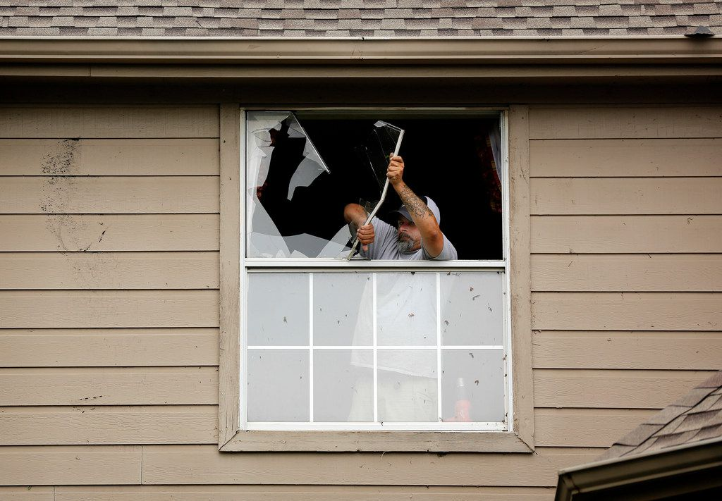 Dan Creel of Armstrong's Glass and Mirror removes a broken window from the home of Randy Lange on Courtright Dr. in North Fort Worth, Wednesday, May 29, 2019. A tornado warned storm passed through the neighborhood near Heritage Trace Pkwy and N. Riverside Dr. breaking off tree limbs and tearing shingles off of homes.
