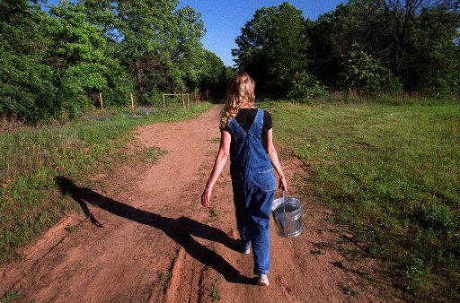 Jeanette Kinman walks down a dirt road to feed the chickens at a spiritual commune called the Adelphi community located  near Terrell about an hour east of Dallas.