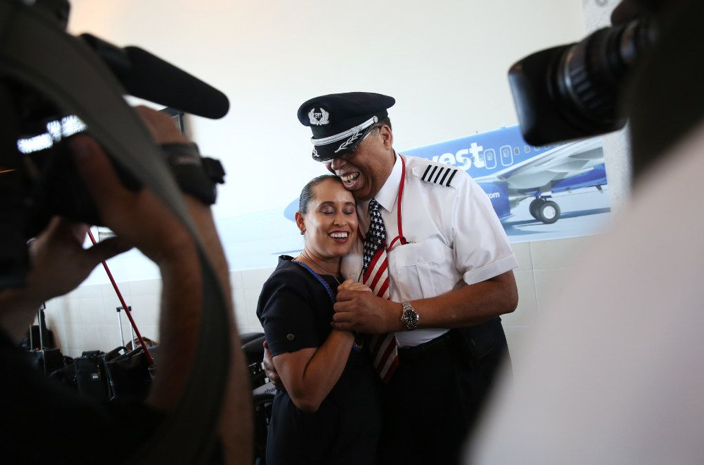 Southwest Airlines' senior pilot Lou Freeman, the first African-American chief pilot of a major U.S. airline, gets a hug from flight attendant Gisela Alvarez before boarding his final flight at Dallas Love Field airport on Thursday.