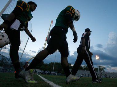 Madison linebacker Kevin Walder (1) and quarterback Travoin Jackson (1) make their way with an official toward midfield for the coin flip against Life Oak Cliff  in the first half of their high school football game at Pleasant Grove Stadium in Dallas, Texas, Friday, September 16, 2016.