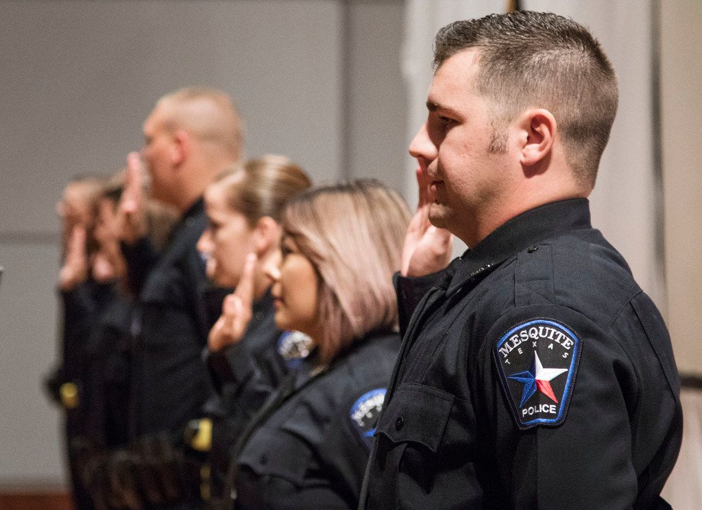 Officer Jeffrey McSpedden of Mesquite raises his hand while being sworn in during graduation from Mesquite police academy.
