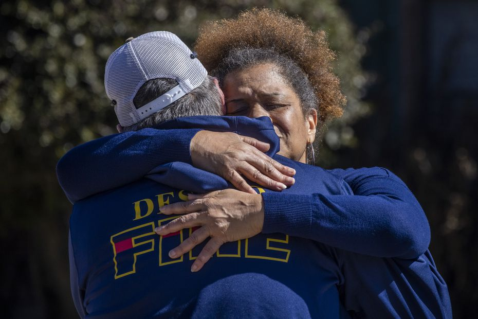 """Sibyl Washington embraces DeSoto Fire Captain Craig Kirk following the aftermath of a house fire on the 100 block of Wildwood Drive that claimed the lives of two small children, ages 1 and 2, on Tuesday morning, Feb. 23. Washington prayed with Kirk on a ledge on her front yard after the fire, she said. """"After he came out with those babies, he was so torn apart,"""" she said. """"He said 'thank you for praying with me,' and I told him I knew he had a tough job and I knew he did all he could."""""""