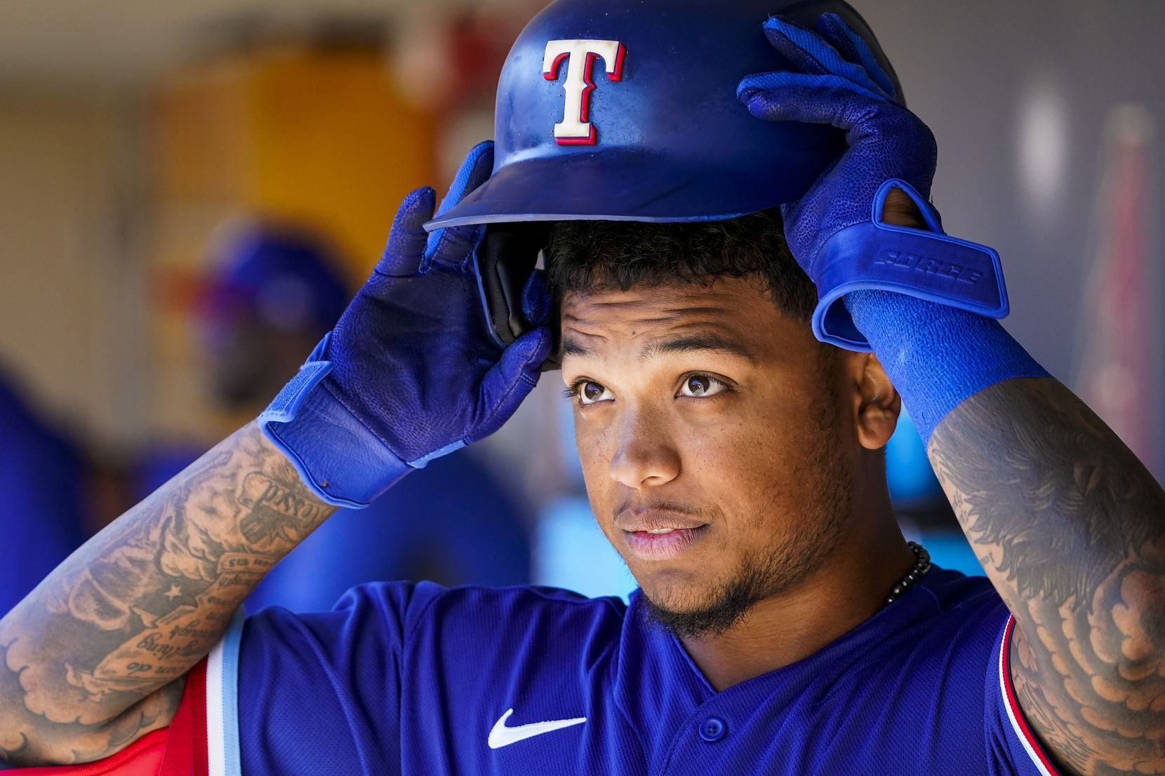 Texas Rangers outfielder Willie Calhoun puts on his batting helmet in the dugout before a spring training game against the Colorado Rockies at Salt River Fields at Talking Stick on Wednesday, Feb. 26, 2020, in Scottsdale, Ariz.