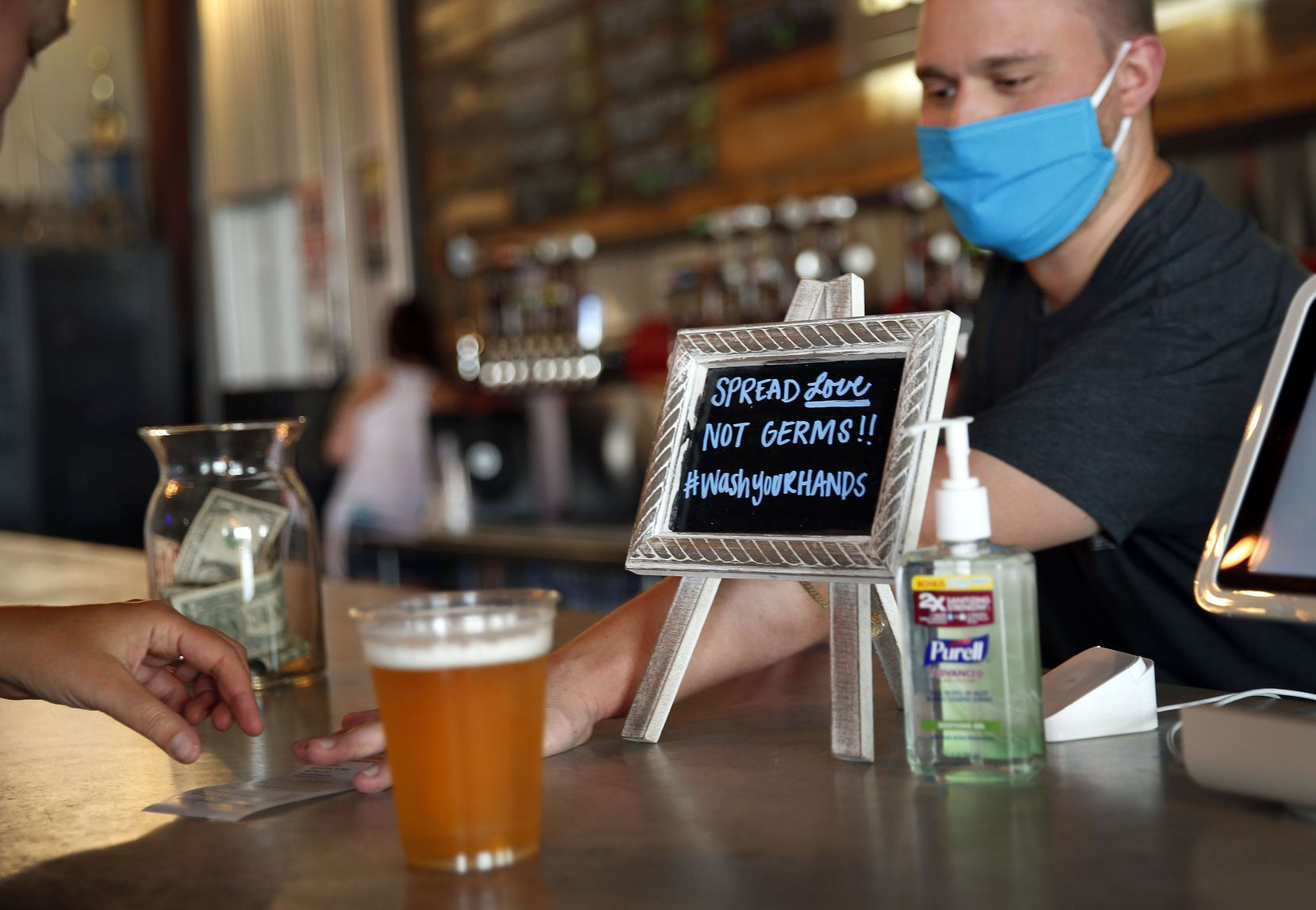 Reminders of the pandemic — masks, hand sanitizer, notes and signs — were plentiful at Legal Draft Company and elsewhere Friday.