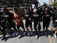 Members of the Austin police department march with members of the University of Texas football team to the State Capitol in Austin, Texas, Thursday, June 4, 2020, during a protest over the death of George Floyd, who died May 25 after being restrained by police in Minneapolis.