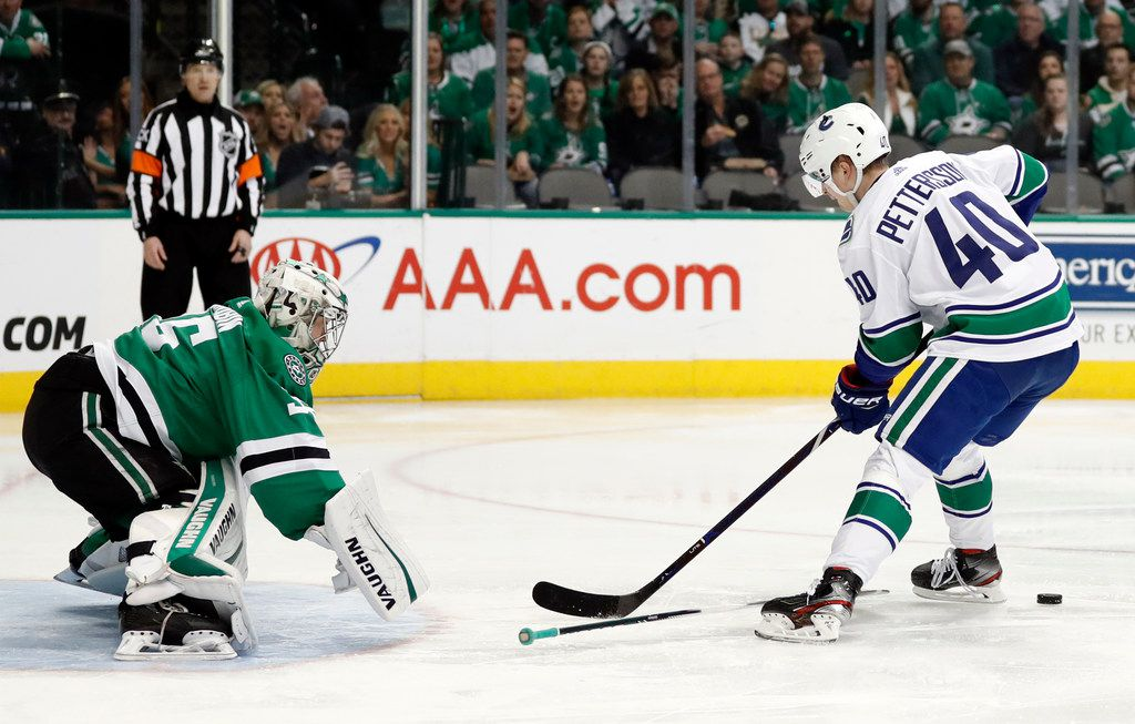 Dallas Stars goaltender Anton Khudobin (35) uses his stick to block a penalty shot attempt by Vancouver Canucks center Elias Pettersson (40) in the second period of an NHL hockey game in Dallas, Sunday, March 17, 2019. (AP Photo/Tony Gutierrez)