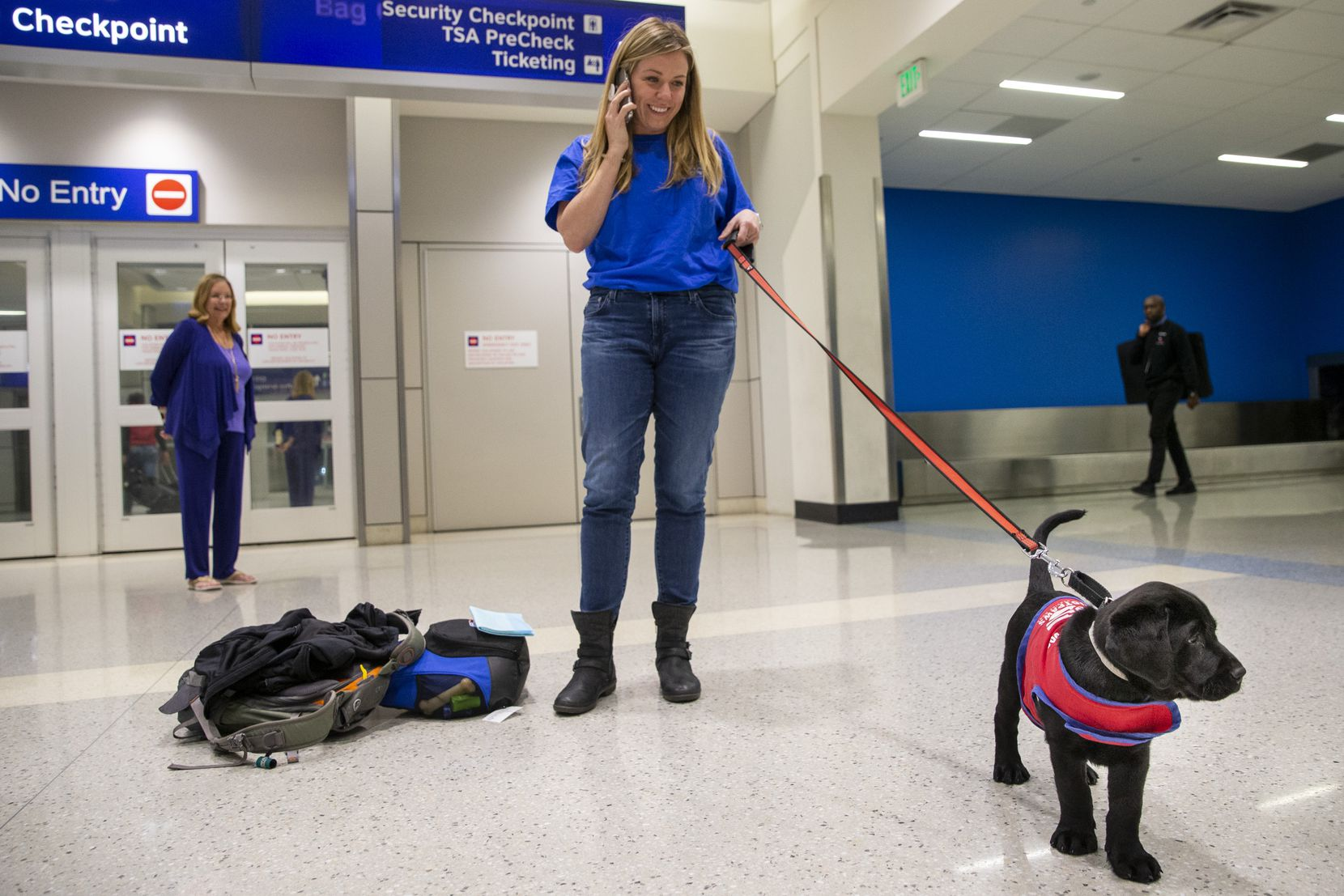 Caroline Clayton, an American Airlines employee, arrives with an 8-week-old lab puppy named Pine to DFW International Airport in Dallas on Saturday, Jan. 25, 2020. Pine the puppy was transported through an American Airlines initiative that allows employees to donate their benefits and miles to transport puppies to be trained as service dogs. Clayton delivered Pine to an employee from Patriot Paws, based in Rockwall, Texas.