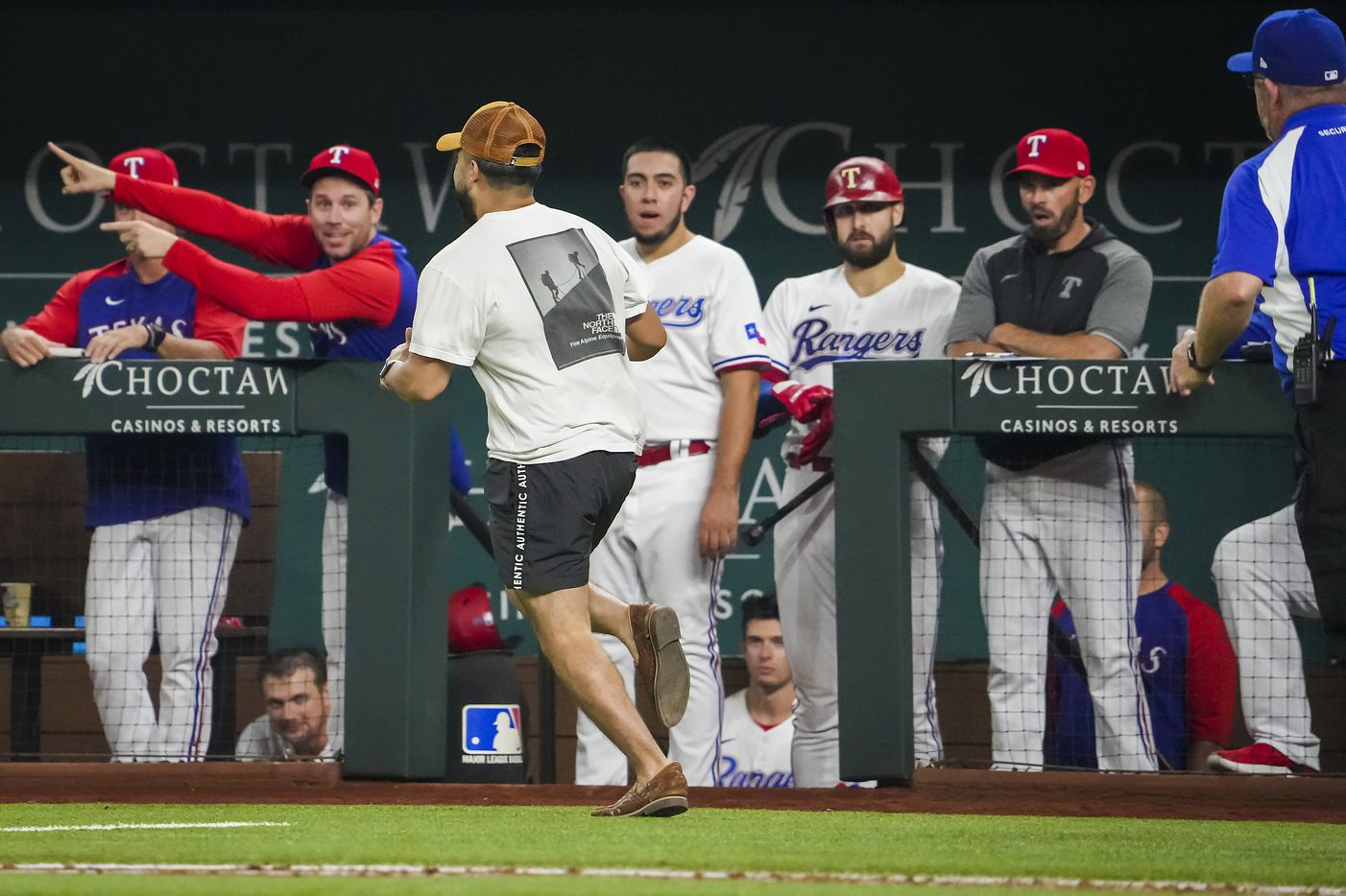 Security guards give chase to a fan who ran out on the field as the Texas Rangers dugout looks on during the eighth inning against the Detroit Tigers at Globe Life Field on Tuesday, July 6, 2021.