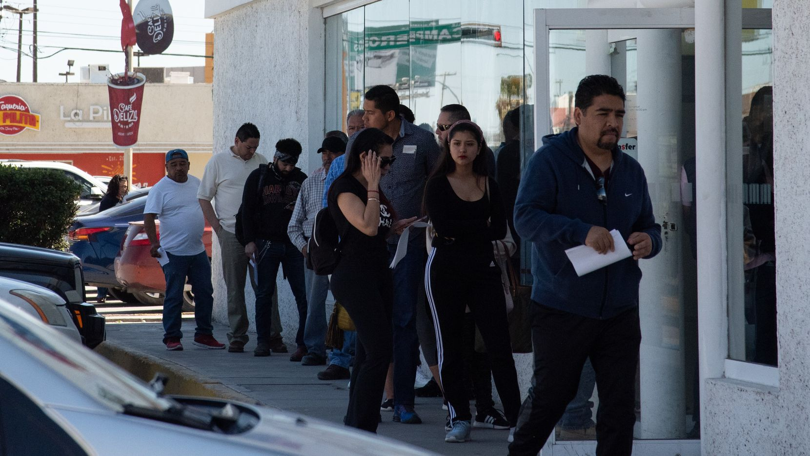 People line up to use an ATM in Ciudad Juarez, Mexico, March 25,2020. Unlike in the bordering city of El Paso, Many in Juarez have not taken warnings to stay home as seriously.