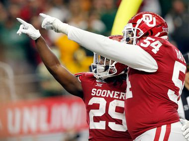 FILE - Oklahoma offensive lineman Marquis Hayes (54) celebrates running back Rhamondre Stevenson's (29) overtime touchdown against Baylor in the Big 12 Championship at AT&T Stadium in Arlington on Saturday, Dec. 7, 2019.