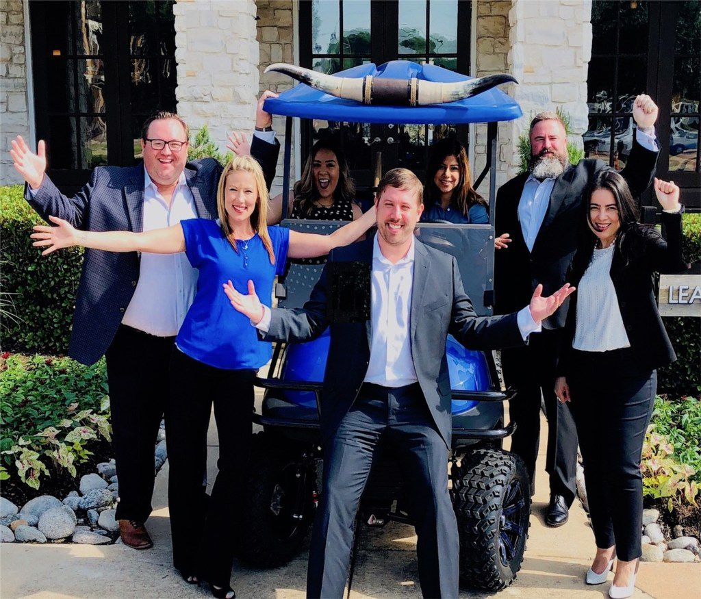 Valiant Residential's leadership team and onsite staff gather around CEO Craig Lashley. The property management company has a fleet of Texas longhorn golf carts to add a little fun to the job.