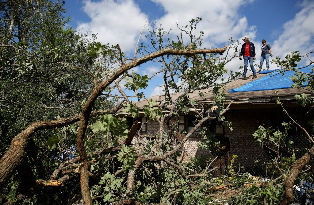 Mitchell Sorsby and Laura Pate survey damage after applying tarps to the roof of Sorsby's parents house after a tornado impacted Emory, Texas on Sunday April 30, 2017. Mitchell's father, Sam Sorsby, is a retired Dallas police officer and guarded the body of Lee Harvey Oswald before his body was released from their custody. Tornadoes whipped through Van Zandt, Henderson and Rains counties Saturday evening with reports of multiple deaths and dozens injured.