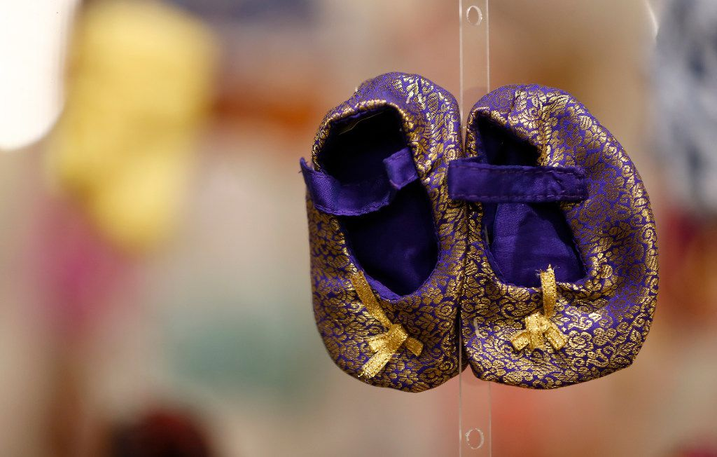 """A pair of baby booties, part of 11,000 pairs collected by the Gendap team last six years, is on display at an exhibit called """"100+ Million Missing"""" hosted by the Gendercide Awareness Project at Fashion Industry Gallery in Dallas, Friday, Feb. 10, 2017. Each pair represents 10,000 missing women and was made by at-risk women in 30 developing countries. (Jae S. Lee/The Dallas Morning News)"""