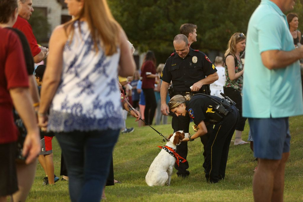 Plano police Officer Hayley Dick reaches down to pet a dog alongside Plano police Sgt. Wes Gerig during National Night Out in the Kings Ridge neighborhood of Plano.
