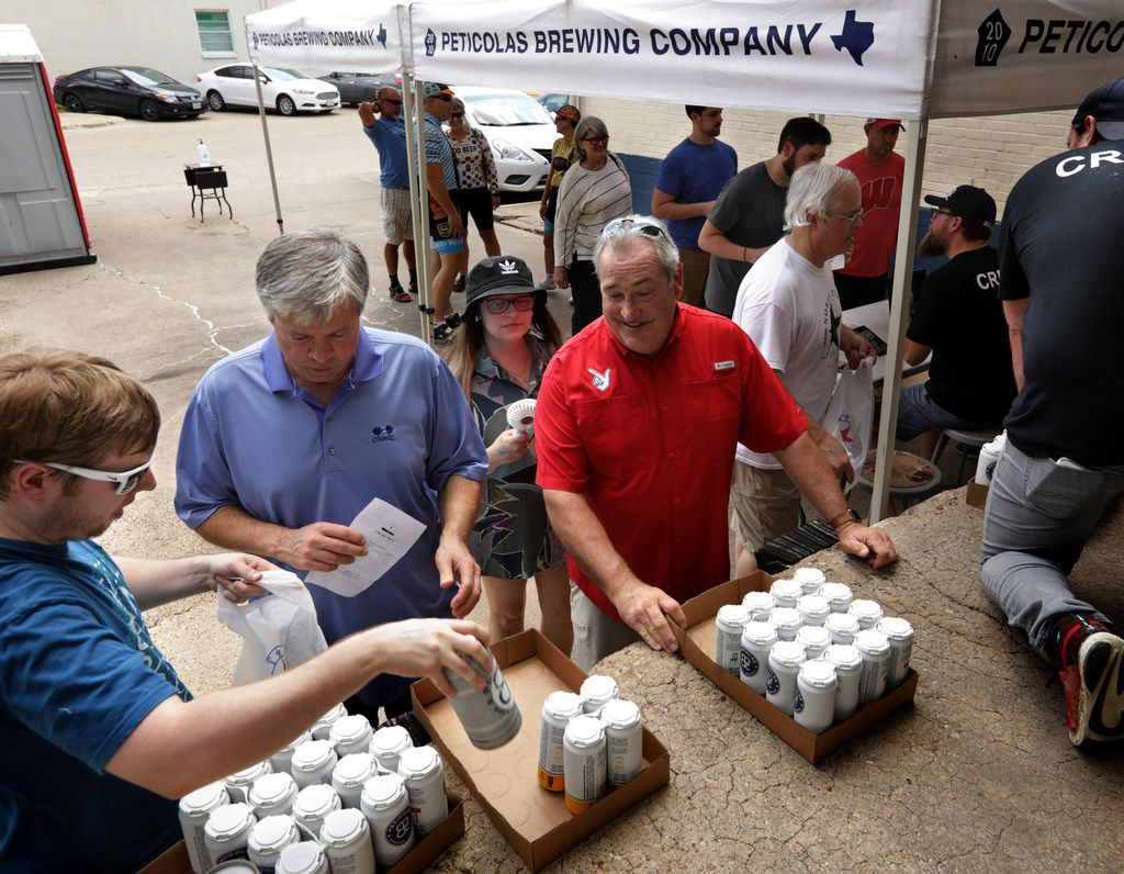 Customers line up to receive their beer purchases at Peticolas Brewing Company in Dallas, TX, on Sep. 1, 2019.