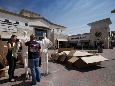 In this 2012 file photo, Tiffany Sola and Kelsey Blum assemble mannequins outside of the Kate Spade store at Grand Prairie's outlet mall. (Brad Loper/The Dallas Morning News)