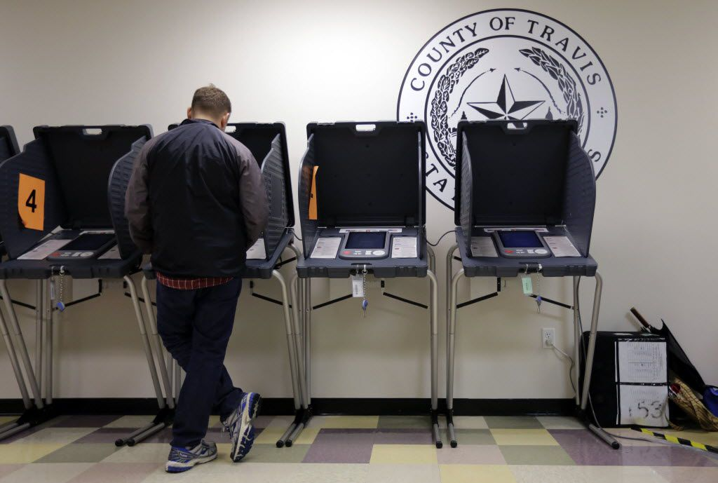A voter casts his ballot at an early voting polling site, in Austin.