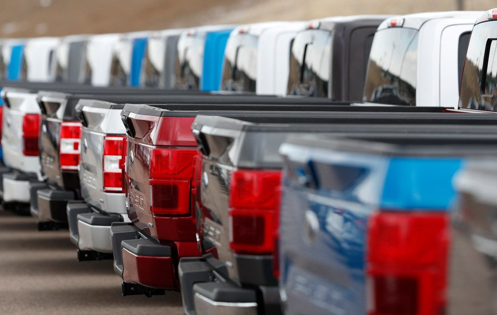 2019 F150 pickup trucks sit in a long row at a Ford dealership in Broomfield, Colo.