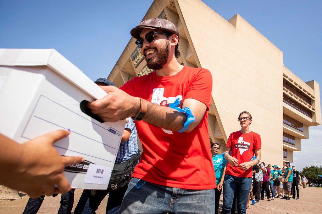 Michael Gonzalez, of the Democratic Socialists of America, helps unload a truckload of boxes as a coalition of labor and faith groups and political activists delivers petitions to at City Hall calling for a city ordinance mandating paid sick time to be placed on the November ballot on Monday, June 11, 2018, in Dallas.