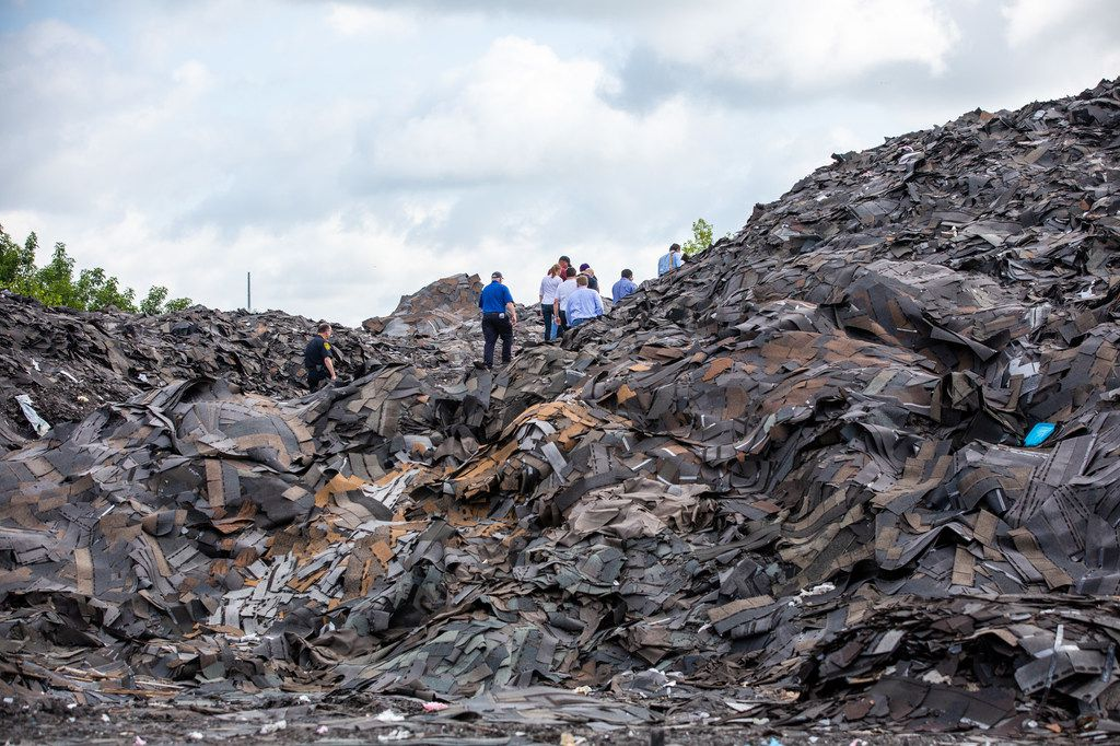 A group of attorneys and city officials, including Judge Gena Slaughter, tours the mountain of roofing shingles that exists at Blue Star Recycling off South Central Expressway in Dallas on  July 2, 2019.