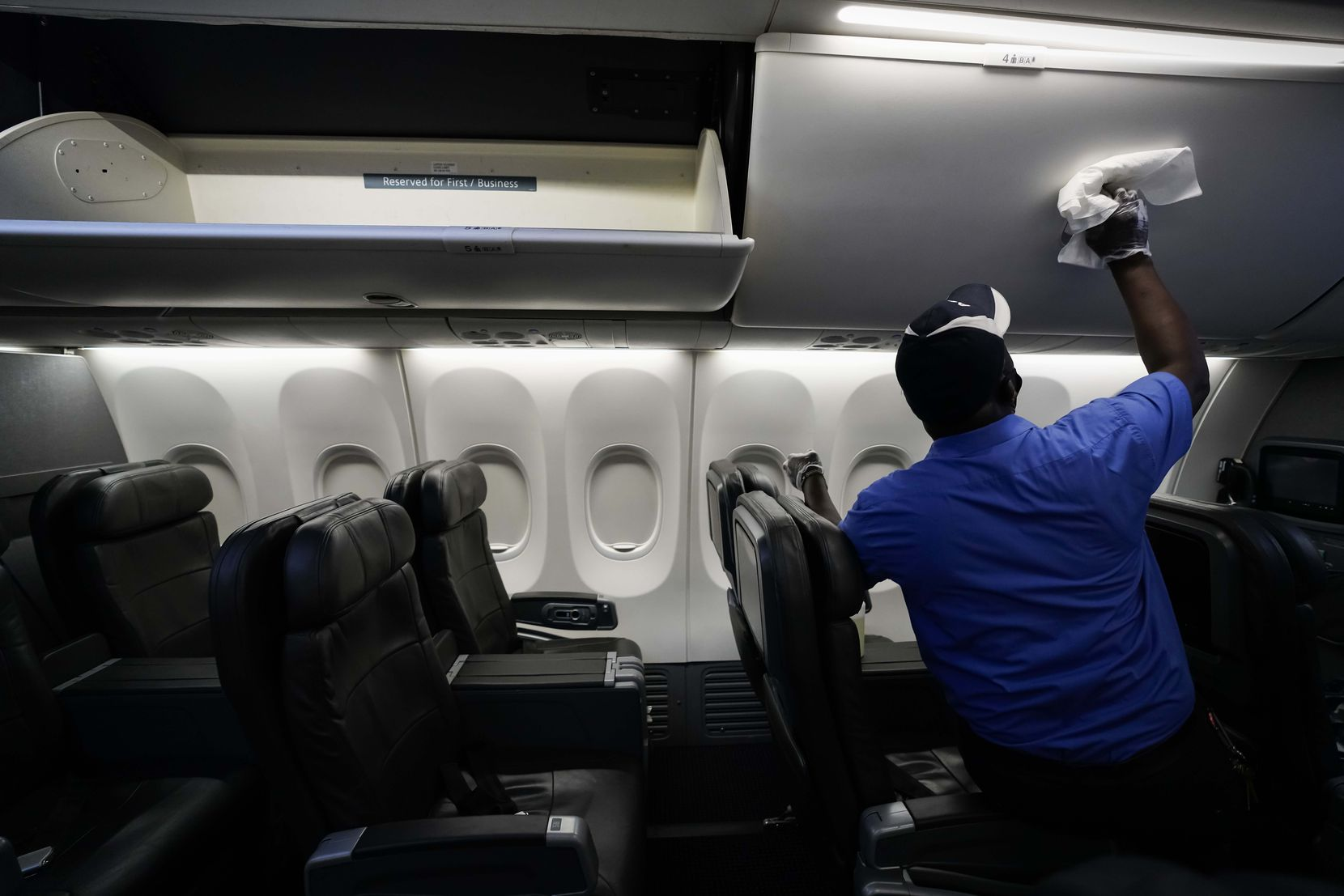 A cabin cleaner with ABM Aviation wipes down the overhead bins of an American Airlines aircraft with disinfectant at DFW International Airport Terminal A on Tuesday.