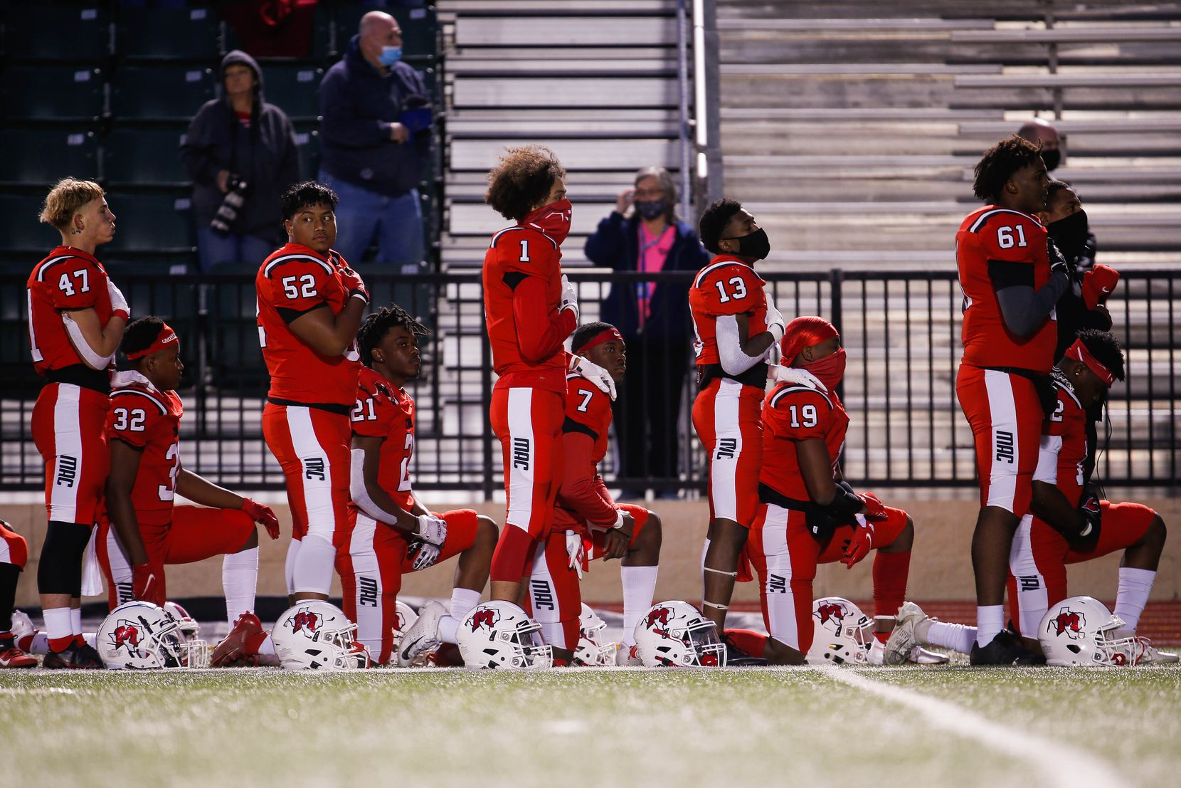 Irving MacArthur High School players kneel and stand during the national anthem before a football game against Lake Highlands at Joy & Ralph Ellis Stadium in Irving on Friday, Oct. 23, 2020. (Juan Figueroa/ The Dallas Morning News)