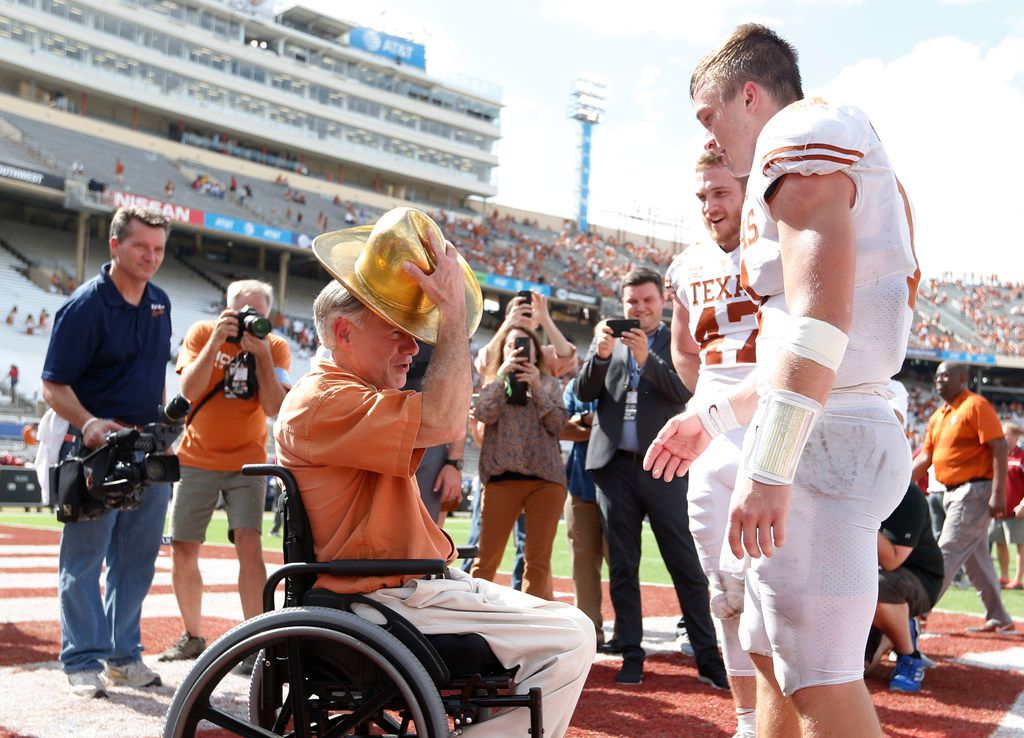 Governor Greg Abbott tries on the golden hat after getting it briefly from Texas Longhorns quarterback Sam Ehlinger (11) after defeating the Oklahoma Sooners 48-45 at the Cotton Bowl in Dallas on Saturday, October 6, 2018. Texas Longhorns tight end Andrew Beck (47) is in the background. (Vernon Bryant/The Dallas Morning News)