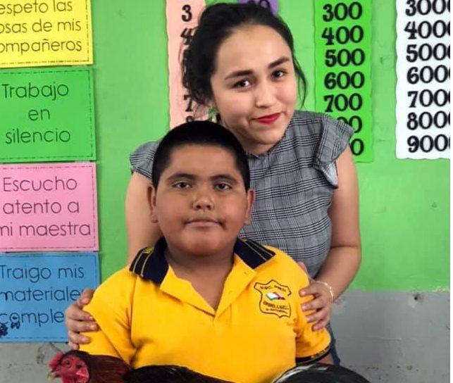 Víctor Manuel le llevó a su maestra Esthefany Guadalupe Gutiérrez uno de los gallos de pelea que él cuida./ AGENCIA REFORMA