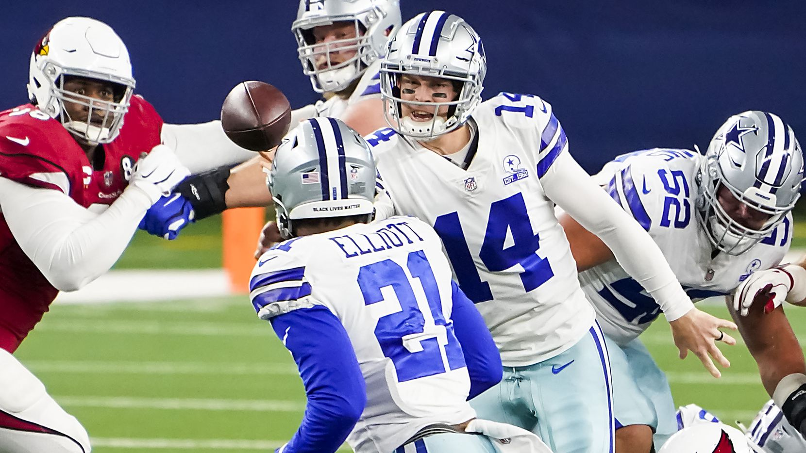 Dallas Cowboys quarterback Andy Dalton (14) gets off a shuffle pass to running back Ezekiel Elliott (21) during the first quarter of an NFL football game against the Arizona Cardinals at AT&T Stadium on Monday, Oct. 19, 2020, in Arlington.