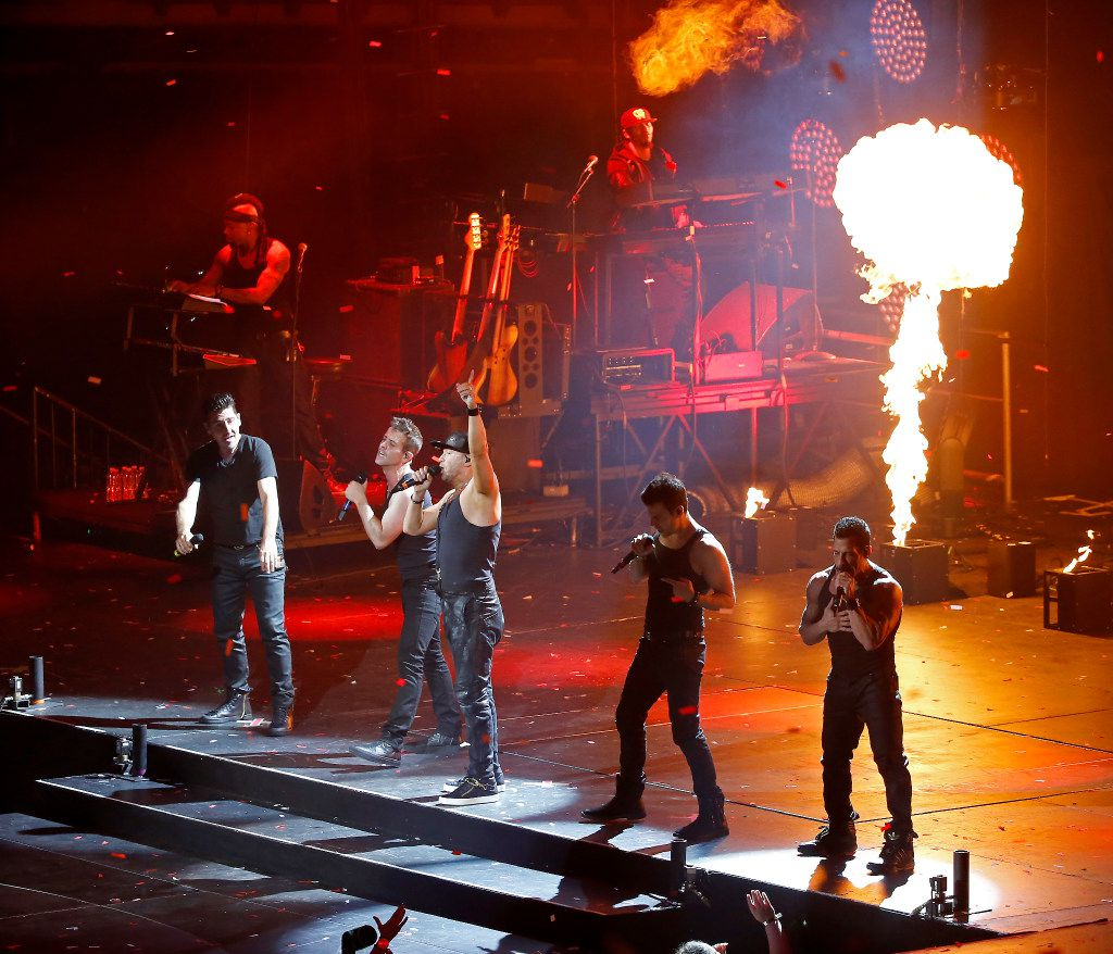Members of New Kids On The Block Donnie Wahlberg, Joey McIntyre, Danny Wood, Jordan Knight and Jonathan Knight perform on stage during the Total Package Tour at American Airlines Center.