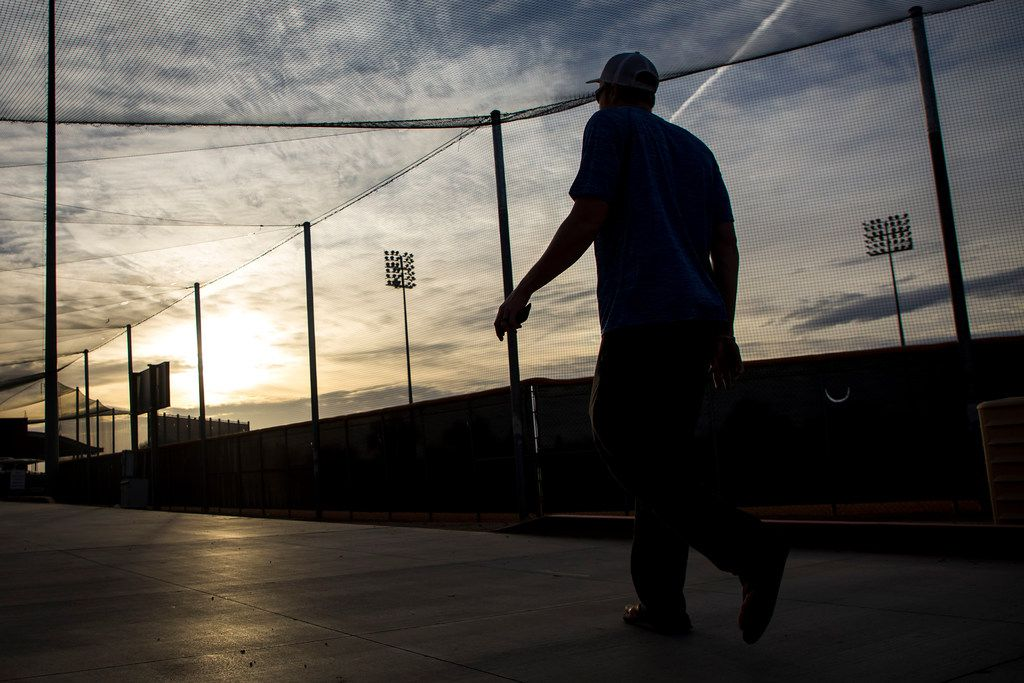 The sun rises over the facility as a Texas Rangers pitcher heads to the clubhouse as pitchers and catchers report for spring training at the team's training facility on Wednesday, Feb. 14, 2018, in Surprise, Ariz. (Smiley N. Pool/The Dallas Morning News)