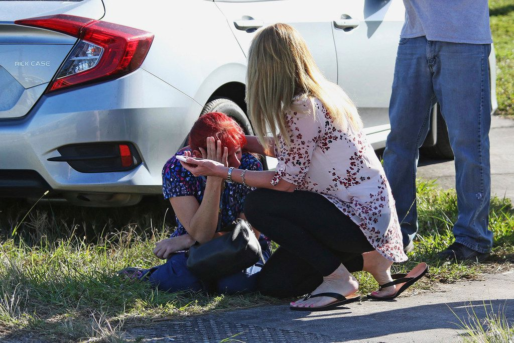 A woman consoles another as parents wait for news regarding a shooting at Marjory Stoneman Douglas High School in Parkland, Fla., Wednesday, Feb. 14, 2018. A shooter opened fire at the Florida high school Wednesday, killing people, sending students running out into the streets and SWAT team members swarming in before authorities took the shooter into custody. (AP Photo/Joel Auerbach)