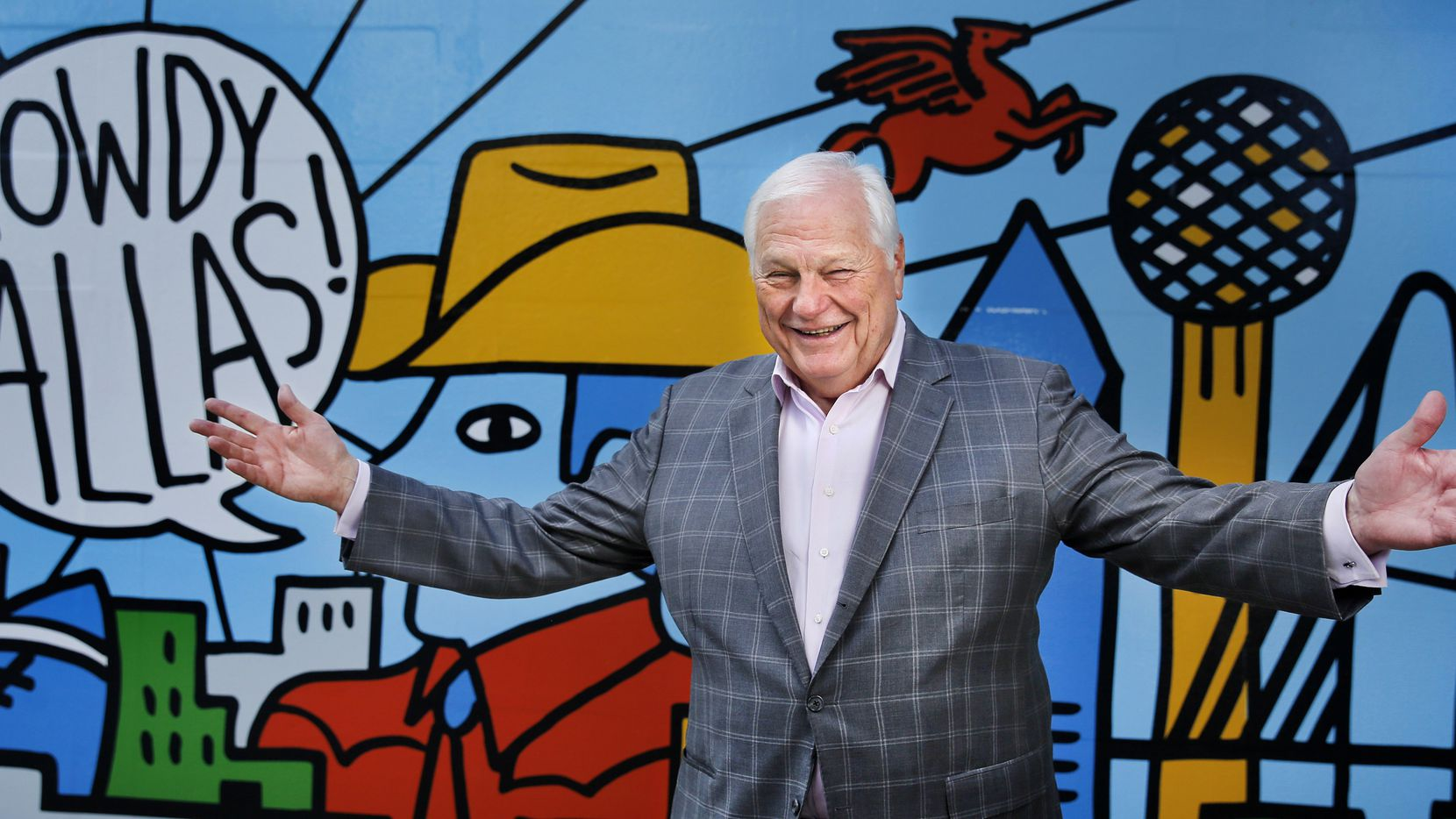 """The Victory Park backdrop for this 2021 photo of WFAA-TV sports anchor Dale Hansen should say """"Farewell,"""" not """"Howdy."""" Hansen retires this week after four decades dominating in local TV news."""