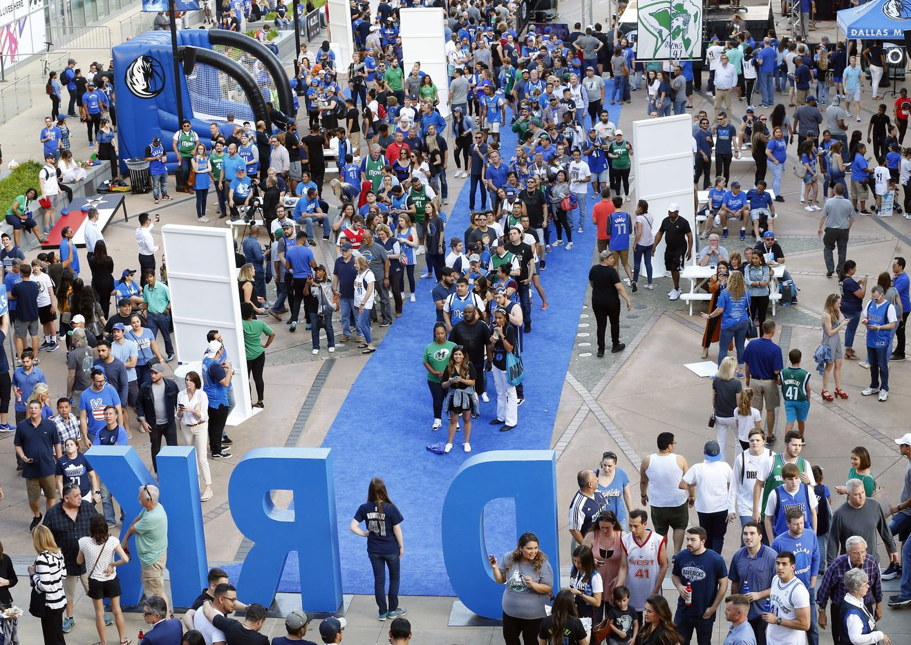Dallas Mavericks fans arrive on the blue carpet and wait to have their photo in the DIRK sign outside American Airlines Center in Dallas, Tuesday, April 9, 2019. This will be Dirk Nowitzki's last home game and will finish out his 21st season this week. (Tom Fox/The Dallas Morning News)